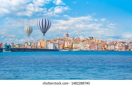 Hot air balloon flying over Galata tower, istanbul - Galata Tower, Galata Bridge, Karakoy district and Golden Horn at morning, istanbul - Turkey