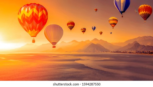 Hot air balloon flying over Antalya . sunset sky and high mountains