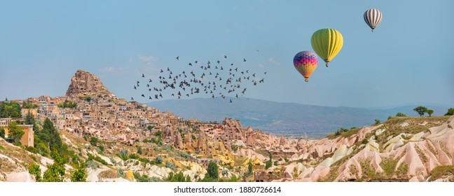 Hot air balloon flying over spectacular Uchisar castle and Pigeon valley - Goreme, Turkey