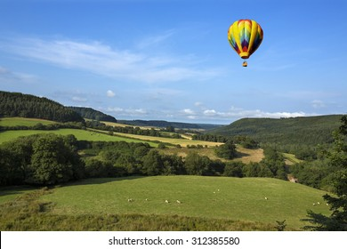 A hot air balloon flying over the countryside of the Yorkshire Dales in the north of England.