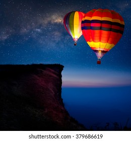Hot air balloon flying over mountain at night