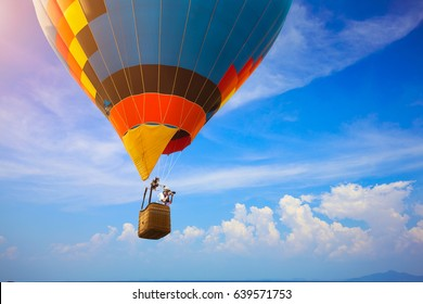 Hot air balloon flying over the sea with photographer