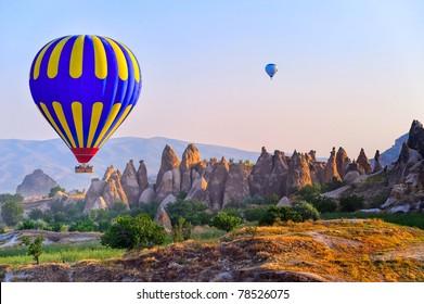 Hot air balloon flying over bizarre rock landscape in Cappadocia, Turkey