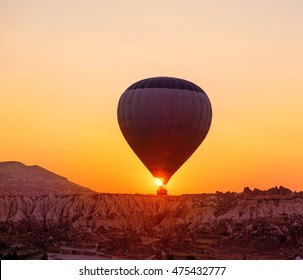 Hot air balloon flying at the sunrise over a volcanic rocks valley in Cappadocia, central Turkey
