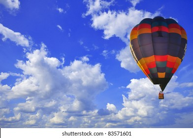 hot air balloon with green field and blue sky