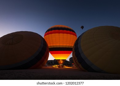 Hot air balloon illuminated between other two still sleeping with beautiful blue sky in background
