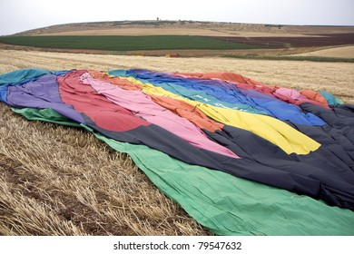 A hot air balloon lying in a field
