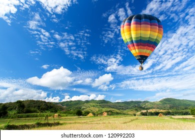 Hot air balloon over the field with blue sky