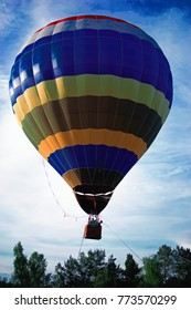 Hot air balloon over the green forest. Composition of nature and blue sky background.