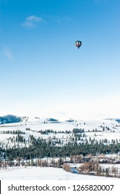Hot Air Balloon Over Mountains in Winter
