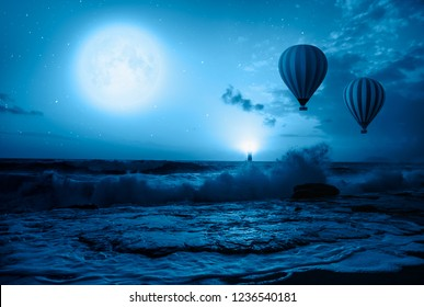 """Hot air balloon over the stormy sea against super blue full moon and lighthouse at night"""" Elements of this image furnished by NASA"""""""