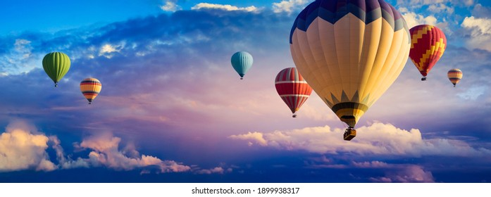 Hot Air Balloon Ride at sunrise background for wide banner of travel agency or adventure tour. Morning hot-air balloon flight with beautiful clouds. Romance of ballooning in a good weather. - Shutterstock ID 1899938317