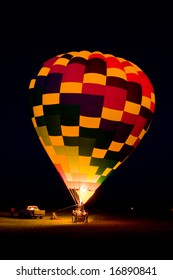 "A hot air balloon team is lighting the balloon's propane burner while its tethered to the ground at night to produce a ""balloon glow""."
