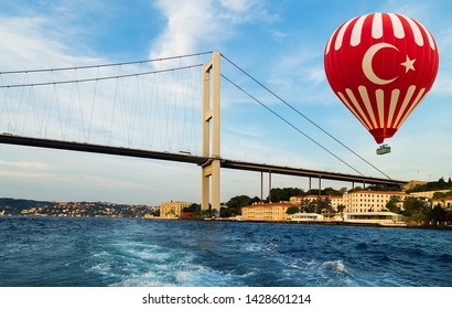 Hot air balloon Turkish flag flying over Istanbul bridge Bosporus. Fatih Sultan Mehmet Bridge Turkey. Travel concept.