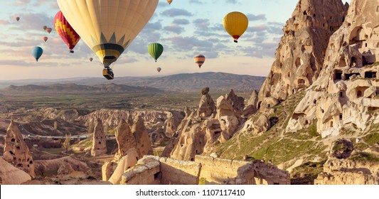 Hot air balloons above Turkish National Park in Goreme. Panorama of Cappadocia landscape - multi colored balloons flying over mountain valley of ancient cave town Uchisar.