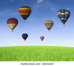 hot air balloons with blue sky on green grass meadow