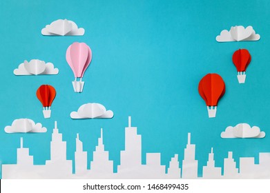 Hot air balloons with clouds above city skyline. Craft paper cut objects photography for banners/landing pages/backgrounds design with copy space.