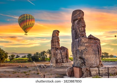 Hot air balloons and Colossus of Memnon in Luxor at sunrise, Egypt
