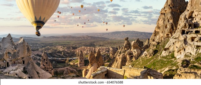 Hot air balloons flight - view of Goreme valley in Turkey. Panorama of Cappadocia - wide angel landscape with colorful hot balloons flying over mountain peaks of ancient cave town Uchisar.