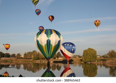 Hot air balloons floating over a river in Prosser, WA.