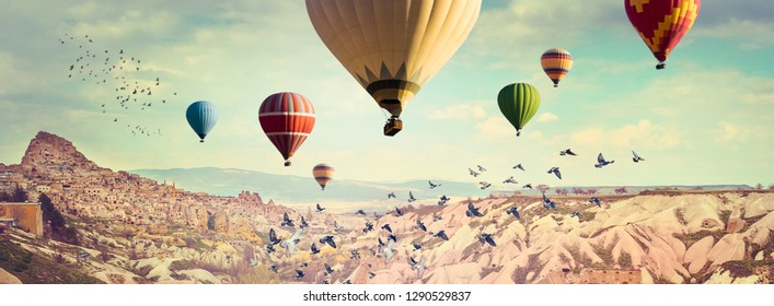 Hot Air balloons flying above the Pigeon`s Valley near the ancient cave town Uchisar. Wide panorama of Cappadocia with multicolored balloons over colorful mountain landscape.