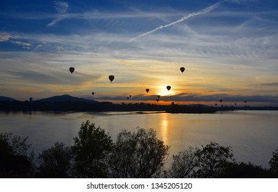 Hot air balloons flying in the air above Lake Burley Griffin, as part of the Balloon Spectacular Festival in Canberra.