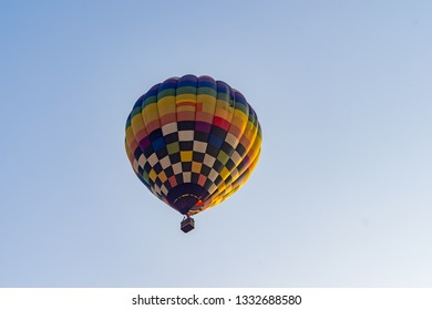 Hot air balloons flying on the blue sky during sunrise in morning.