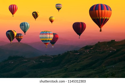 Hot Air balloons flying over road in forest landscape sunset background.