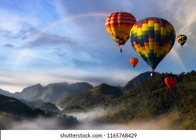 Hot air balloons flying over the mountains and fog in the morning with rainbow at the view point Doi Inthanon view hidden heaven of Chiang Mai.