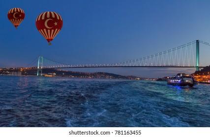 Hot Air balloons flying over Bosphorus Bridge at night. Istanbul, Turkey