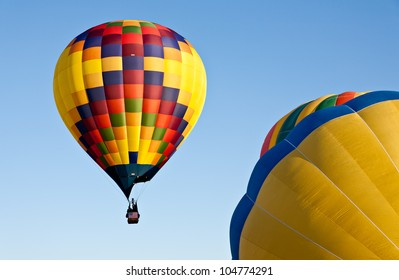 Hot air balloons inflate and ascend in the sky above Colorado Springs