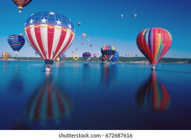 Hot air balloons launch over lake