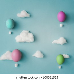 Hot air balloons made of decorated Easter eggs with cotton clouds on bright blue background. Flat lay. Creative concept.