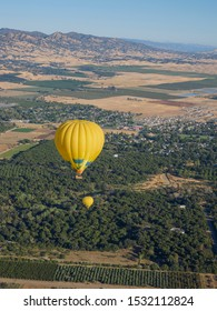 Hot air balloons over farms and mountains of Central Valley