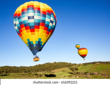 Hot air balloons over Napa Valley vineyards at sunrise with blue sky