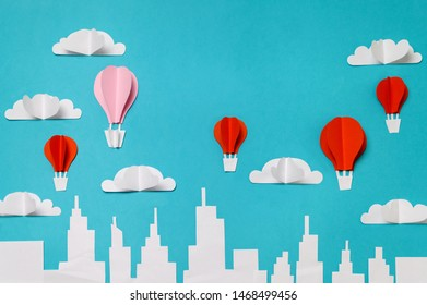 Hot air balloons paper cut objects in the sky above city skyline. Craft paper objects photography for banners/landing pages/backgrounds design with copy space.
