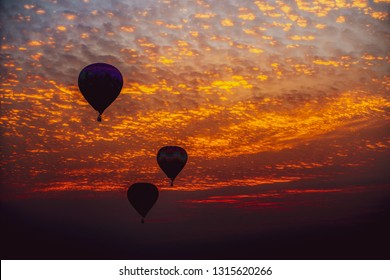 Hot air balloons silhouetted by the rising sun at dawn