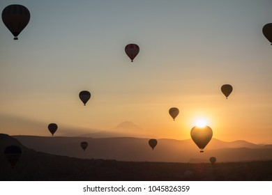 Hot air balloons in the sky during sunrise. Flying over the valley at Cappadocia, Anatolia, Turkey. Volcanic mountains in Goreme national park.