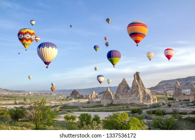 Hot air balloons in the sky over the cave town, Valley of Daggers, Cappadocia, Turkey