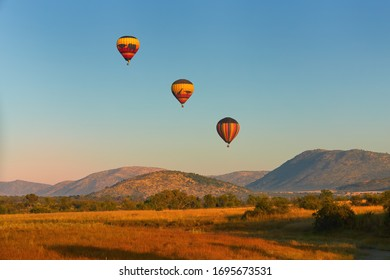 Hot air balloons with tourists above the Pilanesberg reserve. Three hot air balloons, decorated safari motifs against blue sky, mountains on background. Balloons Safari. Holiday in South Africa.