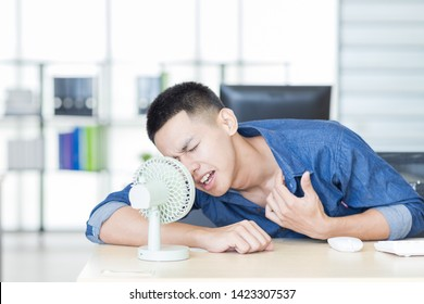 Hot air and broken air conditioning at the same time. The young office staff came back from lunch. He use a portable fan helps relieve heat. Concept Heat Stroke.