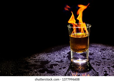 Hot alcoholic cocktail burning in shot glass  on black background.