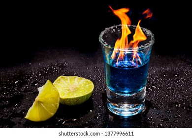Hot alcoholic cocktail burning in shot glass with salt and lime.