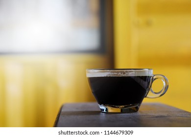 hot Americano coffee or hot black coffee in transparent cup with yellow metal sheet background. have some space for write wording