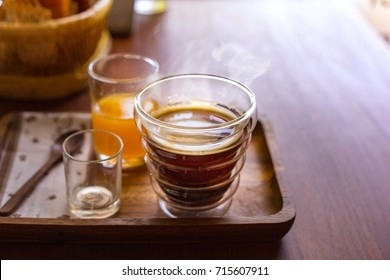Hot americano coffee with orange juice on wooden table.
