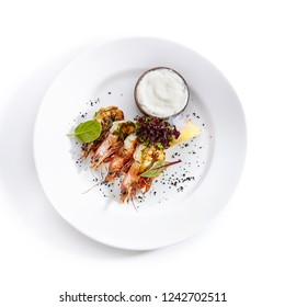 Hot Appetizer of Grilled Tiger Prawns with Green Oil on Elegant Restaurant Plate Isolated on White Background. Warm Starter with Fried King Shrimps with Herbs, Spices, Sauce, Lemon, Greens Top View