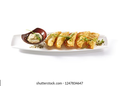 Hot Appetizers with Mini Chebureki, Cheese and Greens Isolated on White Background. Restaurant Starter Menu with Crispy Burnt Turnovers, Pies or Samosa with Spicy Sause and Arugula Close Up