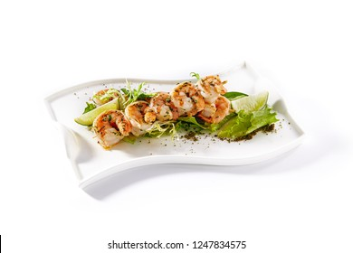 Hot Appetizers of Skewered Tiger Prawns Fried with Garlic on Elegant Restaurant Plate Isolated on White Background. Warm Starter with Grilled King Shrimps with Herbs, Spices, Lime and Greens Close Up
