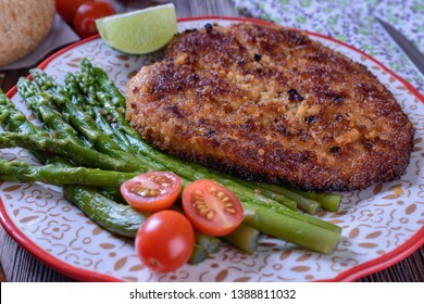 Hot appetizing schnitzel with crispy crust on a plate next to asparagus, lime and cherry tomatoes on a wooden table are ready for eating