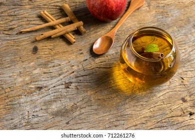 hot apple juice in glass with cinnamon on old wood. autumn food concept